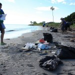 A volunteer with the NOAA-funded Protectores de Cuencas project records debris data on a beach in Puerto Rico. (Credit: NOAA)